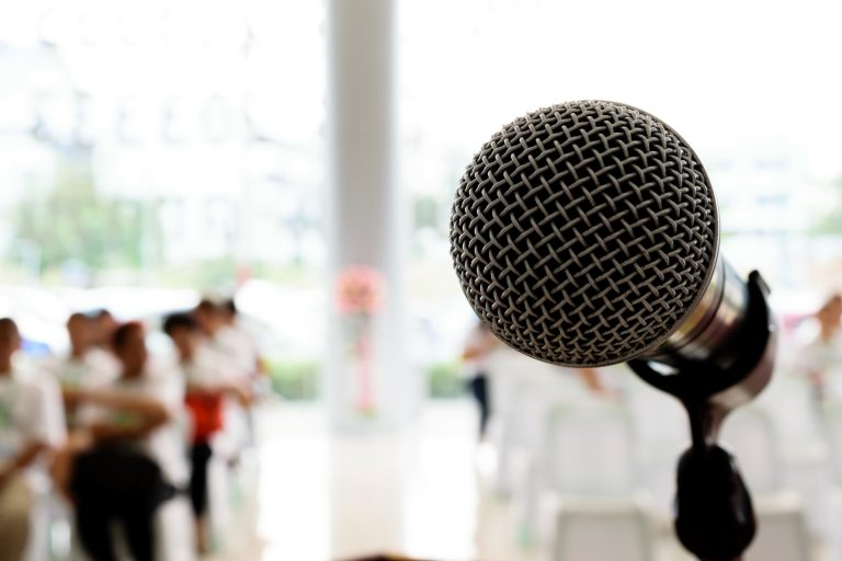 Microphone in concert hall or conference room with defocused person in background.
